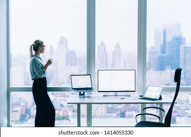 Side view of elegant relaxing woman in glasses having cup of coffee while looking away in big window with cityscape behind