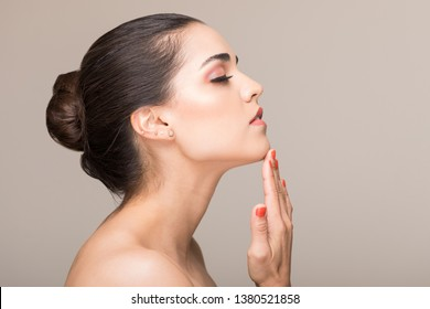 Side view of elegant woman with raised head touching her chin over isolated background
