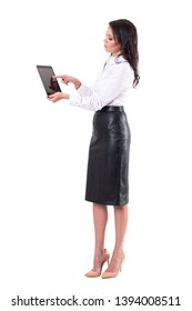 Side view of elegant young business woman using interactive tablet touch screen. Full body isolated on white background.