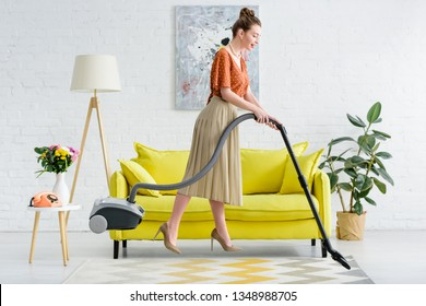 side view of elegant young woman levitating in air while vacuuming carpet