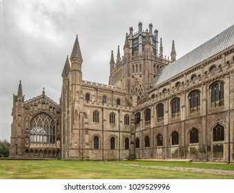 A side view of Ely Cathedral in autumn.  Overcast sky and green grass area in the foreground. 87