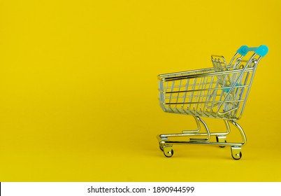 Side view of an empty shopping cart on yellow background with copyspace. retail store