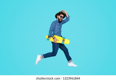 Side view of energetic man in hat and sunglasses holding yellow longboard and jumping up on blue background