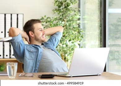 Side view of an entrepreneur relaxing and thinking sitting in a desktop and looking through a window at office