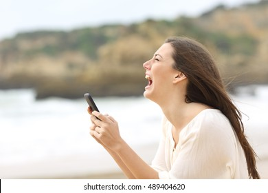 Side view of a exaggerated girl using a smart phone on line and crying desperately with eyes closed on the beach