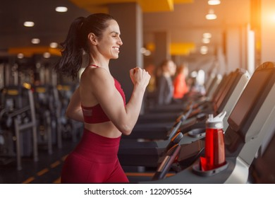 Side view of excited female in sportswear smiling and running on treadmill while exercising in modern gym