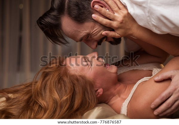 Side view of excited man is lying over woman in bed. They are looking at each other eyes and laughing