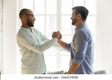Side view excited mixed race male friends in eyewear shaking hands. Happy best buddies welcoming each other at sudden meeting. Smiling coworkers saying hi, communicating together indoors.