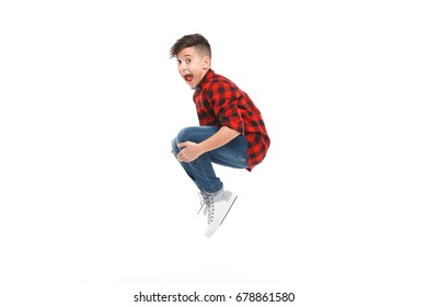 Vue latérale de jeune garçon excité sautant isolé sur fond blanc.