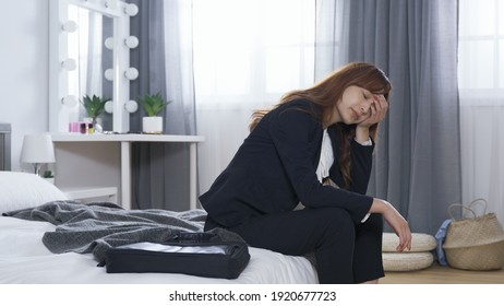 side view exhausted woman in business wear coming back home, kicking off high heels while seated on bed. tired female leaning forward covering face. meeting with a defeat at work concept.