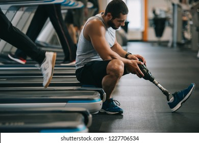 side view of exhausted young sportsman with artificial leg sitting on treadmill at gym