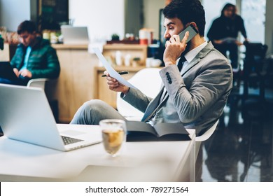 Side view of experienced confident proud ceo talking with economist on mobile phone during checking banking reports to consultancy about some questions.Lawyer in formal wear calling to colleague
