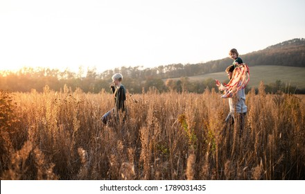 Side view of family with small daughter on a walk in autumn nature. - Shutterstock ID 1789031435