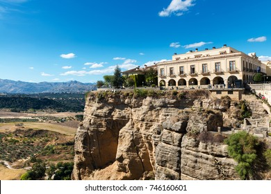 Side view of the famous Parador built over the cliff of the Guadalevin river in the Andalusian village of Ronda, Spain, as seen from the Puente Nuevo bridge.