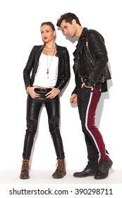 side view of a fashion couple in leather jackets standing in studio and look away from the camera