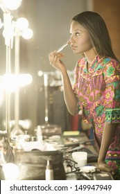 Side view of a fashion model applying makeup in dressing room mirror