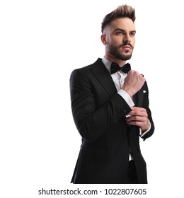 side view of fashion model in tuxedo fixing cufflinks and looks away from the camera on white background