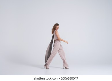 Side view of fashion model wearing trend clothing looking at camera