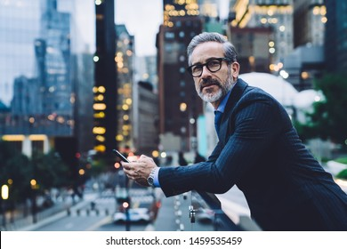 Side view of fashionable pensive gray haired businessman in black coat and glasses texting on smartphone leaning on glass fence and looking away on blurred background in New York