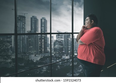Side view of fat Asian man staring at the cityscape pensively while standing by the window in his office