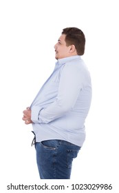 A side view of a fat man shows the tight clothing, trying to close the buttons of the shirt, isolated on a white background.