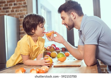 Side view of father and son eating citrus fruits in kitchen