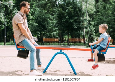side view of father and son having fun on swing at playground in park