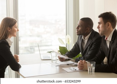 Side view of female applicant introducing herself during job interview, talking about working experience, multiracial recruiters hr managers interviewing listening to candidate, considering cv resume