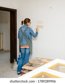 Side view of female architect woman testing light paint on the renovated room wall during the general reconstruction of her dream house