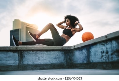 Side view of a female athlete doing abdomen crunches on rooftop fence of a building. Female athlete doing fitness training on rooftop with sun flare in the background.
