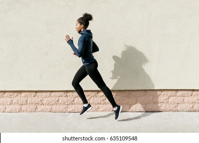 Side view of female athlete running against wall
