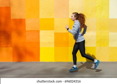 Side view of female athlete running against bright colorful graffiti wall, copy space
