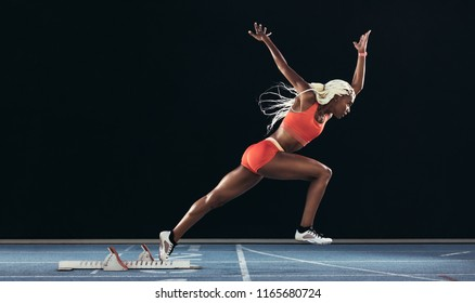 Side view of a female athlete starting her sprint on a running track on a black background. Runner using starting block to start her run on a running track.