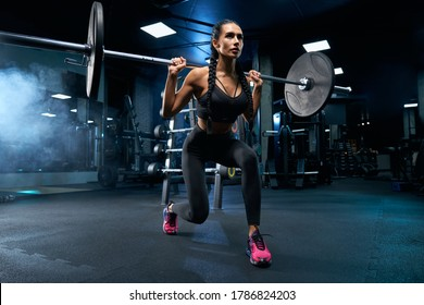 Side view of female bodybuilder with braids doing lunges using barbell. Srtong brunette woman with muscular body in sportswear training legs in gym in dark smoky atmosphere. Weightlifting concept.