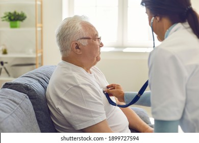 Side view of a female doctor listening to the heart and breathing of an older man through a stethoscope on his chest. Man sitting on sofa at home. Concept of medical care for the elderly at home.