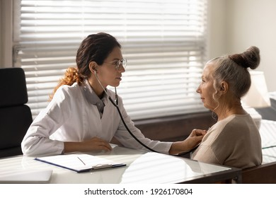 Side view female doctor wearing glasses using stethoscope, checking mature patient lungs at meeting, listening to heartbeat, old woman breath, elderly generation healthcare, medical checkup concept