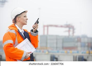 Side view of female engineer using walkie-talkie in shipping yard