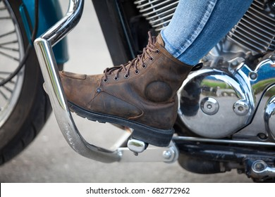 Side view at female foot with protective boot on the stands of chopper motorbike, close up