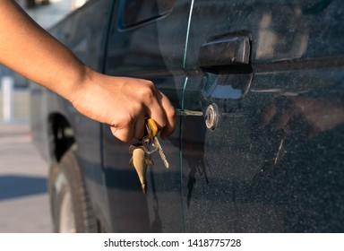 Side view of female hand in bright sunlight inserting a car key in to a door lock of a pickup truck - Tanned hand unlocking the door of an auto vehicle at sunset with metal keys