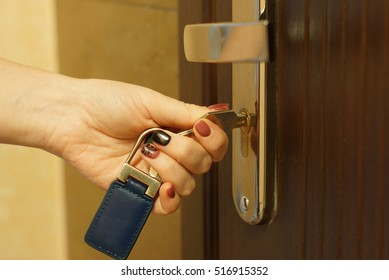 Side view female hand holding key to insert in door lock