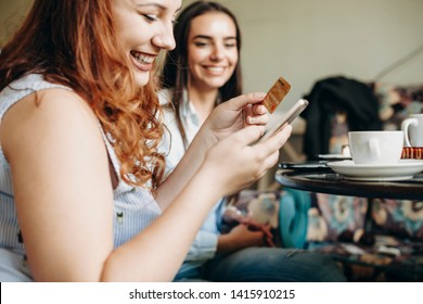 Side view of a female hands using a credit gold card and a smartphone for online banking while sitting a desk in coffee shop with a female friend smiling.