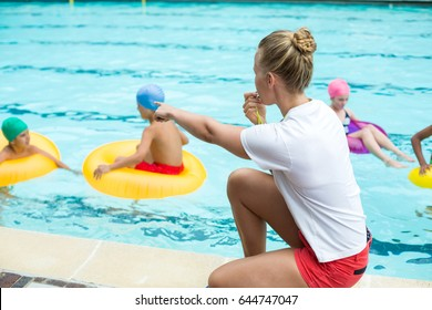 Side view of female lifeguard whistling while instructing children in swimming pool