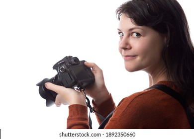 Side view of a female photographer holding a camera isolated on a white background for composites.  The model is posed to face a scenery or copy space