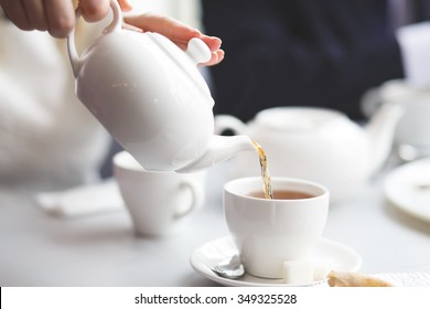 side view of a female pouring tea