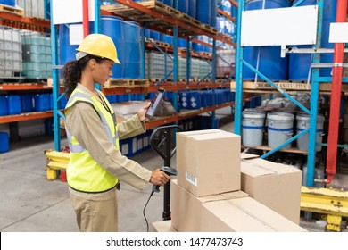 Side view of female worker scanning package with barcode scanner while using digital tablet in warehouse. This is a freight transportation and distribution warehouse. Industrial and industrial workers