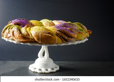 Side view of a festive Mardi Gras King Cake with green, gold, and purple frosting on a white cake stand with a gray background; landscape view
