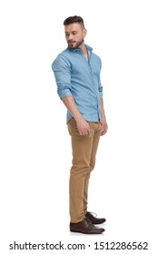 side view of a fit casual man with blue shirt  standing and looking back over the shoulder pensive on white studio background