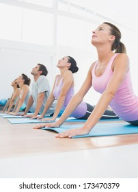 Side view of a fit class exercising in row at fitness studio