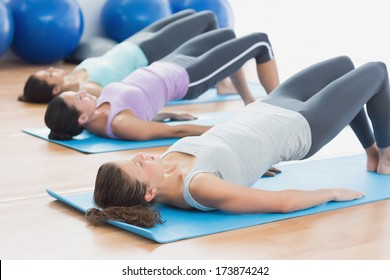 Side view of fit class exercising in row at fitness studio