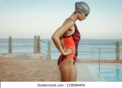 Side view of fit woman swimmer concentrating at pool with her hands on hips. Competitive female swimmer wearing swim cap and goggles near swimming pool at seaside.